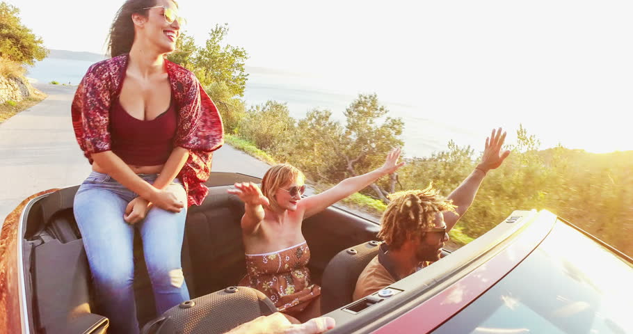 Attractive young caucasian woman sitting on hood of convertible car and dancing to music while riding with her friends at sunset, graded | Shutterstock HD Video #24811778