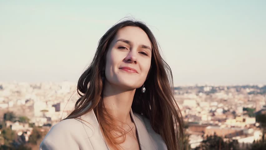 Portrait of young attractive woman standing on observation deck. Girl enjoying sunny day. Rome, Italy on a background.   Shutterstock HD Video #24813845