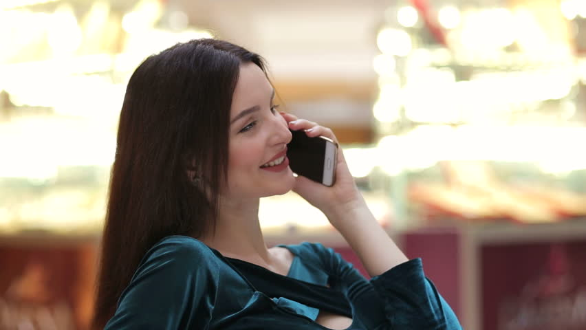 Happy shopper girl calling on the phone. Lovely shopping girl talking on the phone in mall. | Shutterstock HD Video #24821249