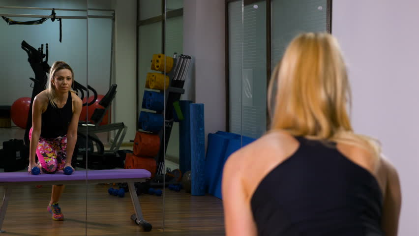 Fit attractive woman working out on exercising device and lifting dumbbells | Shutterstock HD Video #24836570