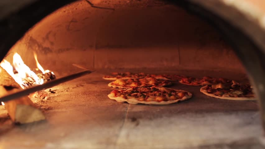 Food, italian kitchen and cooking concept - peel placing pizza baking in oven at pizzeria