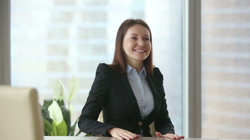 Young happy beautiful businesswoman wearing formal suit meeting casual client at modern office. Negotiations and work with documents between colleagues or partners. Young man choosing consultant