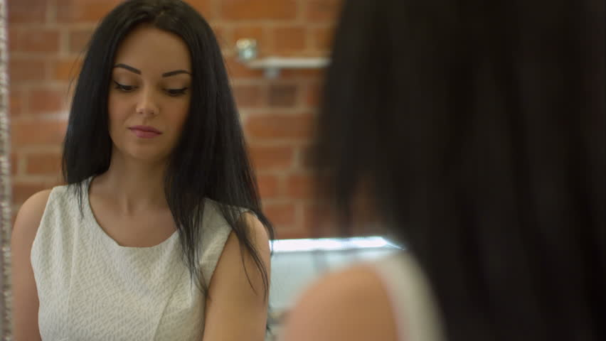 Reflection of young beautiful brunette trying on hair accessory, looking in a mirror | Shutterstock HD Video #24860924