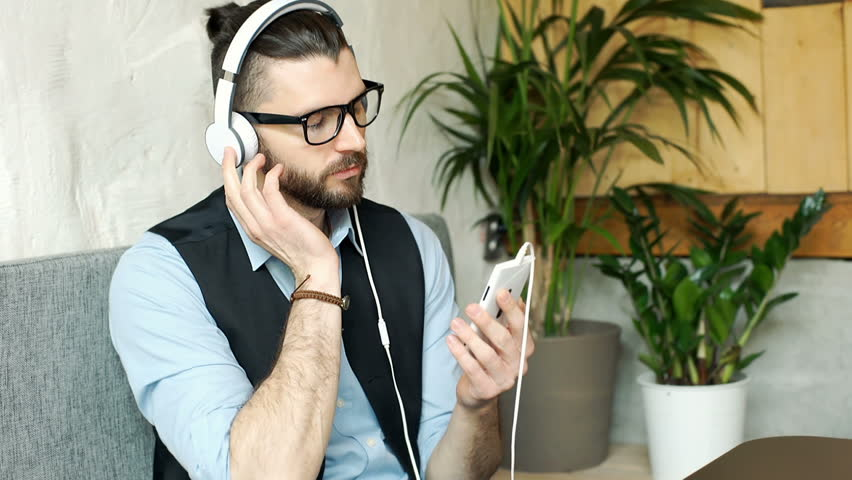 Businessman listening music on headphones and smiling to the camera, steadycam shot  | Shutterstock HD Video #24862346