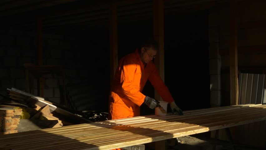 Impregnation and imbibition of arranged wooden bars with a brush. Construction and painting works with wood. Varnishing and gloss of wood in the attic. Sunset sunlight and shadows. Royalty-Free Stock Footage #24864656