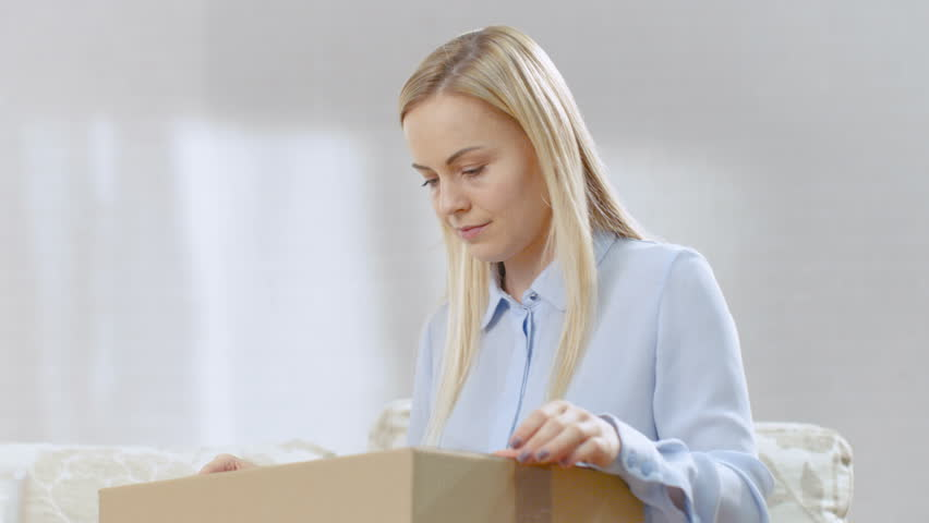 Beautiful Young Woman at Home Opens Cardboard Box while Sitting on a Couch in Her Bright Living Room. She Smiles. Shot on RED EPIC-W 8K Helium Cinema Camera. Royalty-Free Stock Footage #24874232