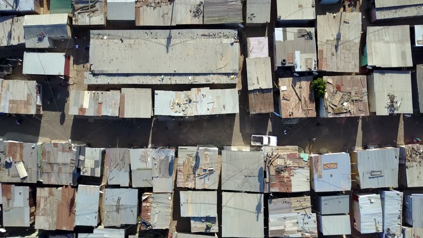 Aerial top-down view of slum a heavily populated urban informal settlement characterized by substandard housing and squalor showing people walking through streets and rusty metal home roof tops 4k | Shutterstock HD Video #24882983