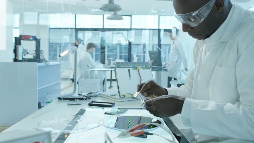 4K Electronics engineers working in lab building & testing circuitry & robotics Royalty-Free Stock Footage #24884300