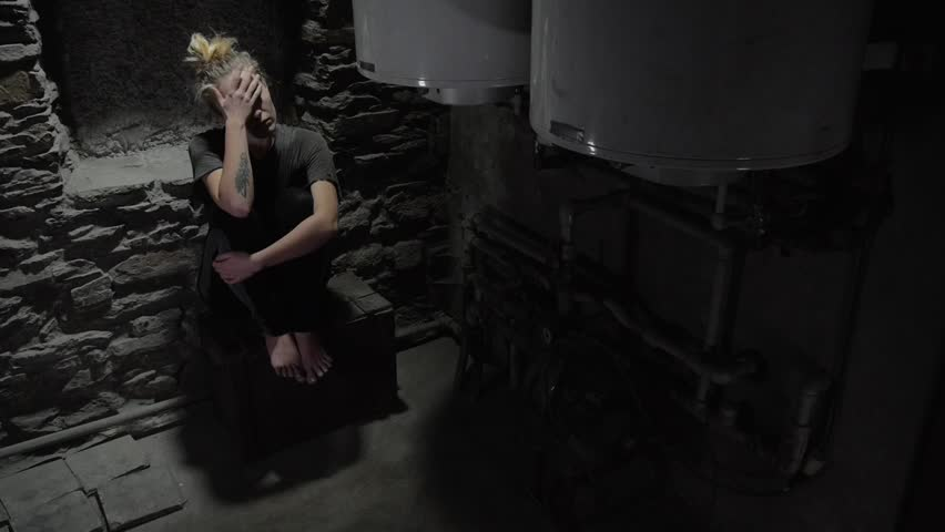 Depressed anxious woman sitting in a dark corner of a basement, blinking overhead light  | Shutterstock HD Video #24885344
