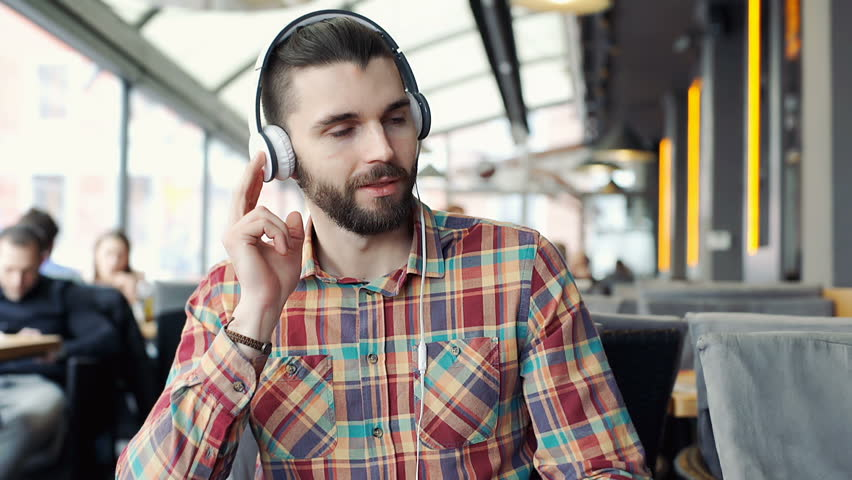 Handsome man in colorful shirt looks happy while listening music in the cafe  | Shutterstock HD Video #24895580