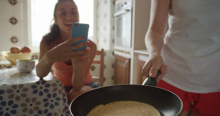 Best Friends making home made Pancakes girl taking photo using smart phone Lifestyle Woman at home sharing on social media #24911234