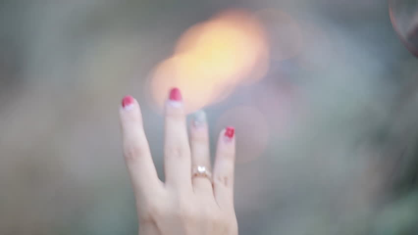 Young woman with beautiful nail polish wearing a diamond ring on her finger
