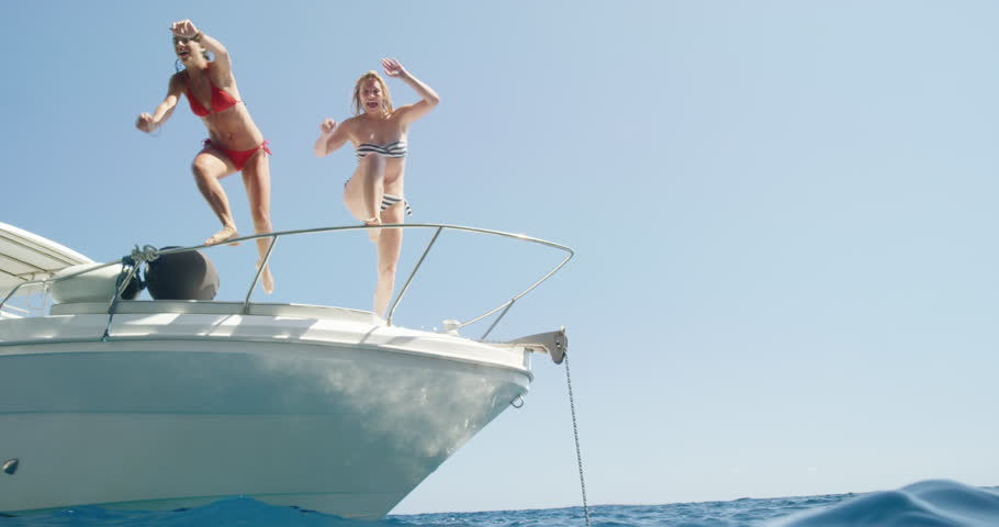 Women jumping off boat into ocean two girls jump into clear blue water from sailboat enjoying active lifestyle summer holiday travel vacation adventure #24912911