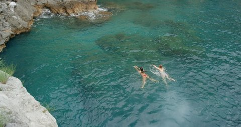 Top view of two women swimming in ocean Girl swimmers enjoying European summer holiday travel vacation adventure in Amalfi Coast Italy