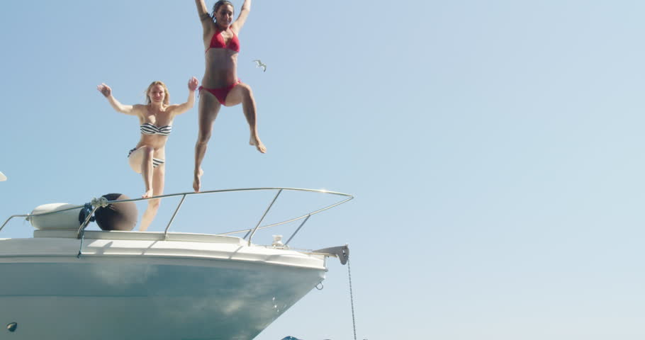 Women jumping off boat into ocean two girls jump into clear blue water from sailboat enjoying active lifestyle summer holiday travel vacation adventure | Shutterstock HD Video #24913460