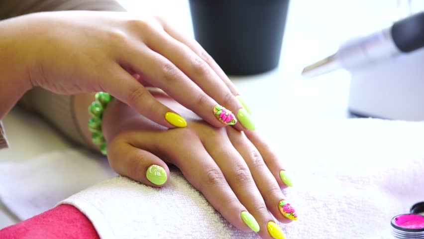 Closeup shot of a beautician applying nail polish to female nail in a nail salon. Close up of a woman hand with yellow nail polish after the manicure.