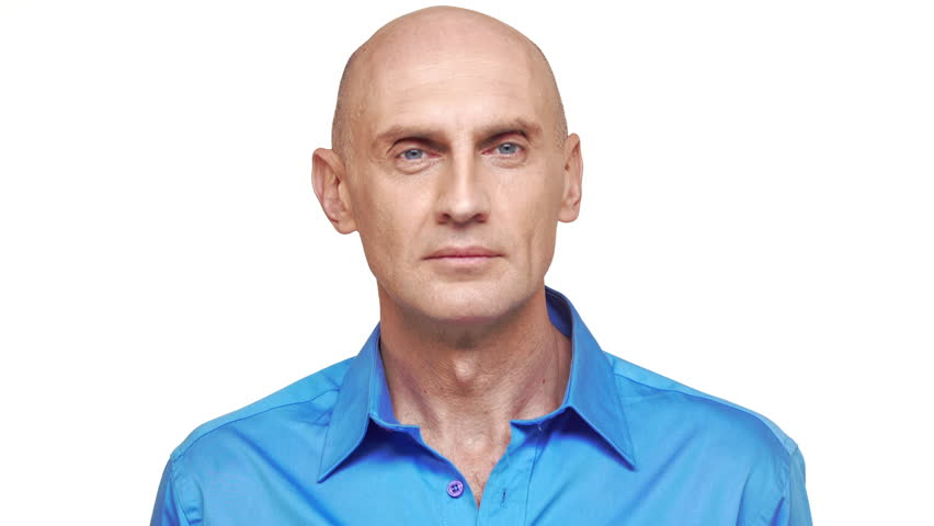 Bold confident Caucasian middle-aged male in blue shirt standing on white background looking at camera on white background