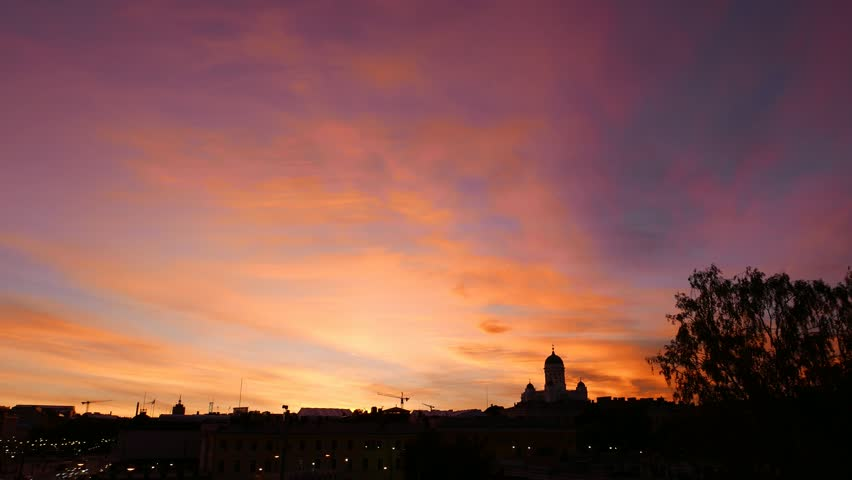 Burning and colorful sunset, vivid transparent clouds run at purple afterglow on darkening sky, saturated afterglow change to darkness. Timelapse shot, black city skyline, Helsinki Cathedral domes