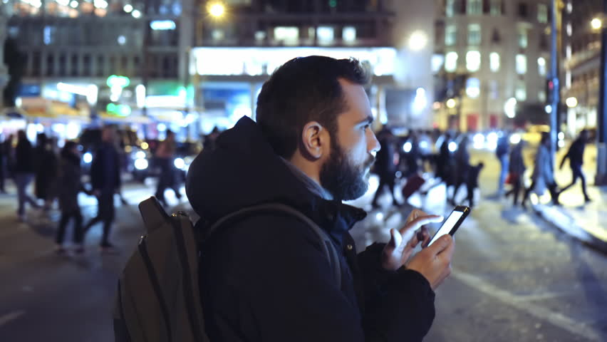 A young man is commuting to work while browsing his cellphone on a busy urban street at night. | Shutterstock HD Video #24940412