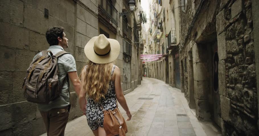 Rear view tourist woman Walking narrow streets of Barcelona Wearing cute summer dress enjoying European summer holiday travel vacation adventure