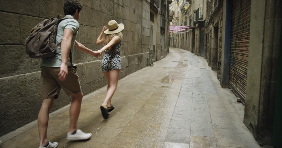 Young couple holding hands woman leading boyfriend walking down European street in Barcelona Spain POV travel concept