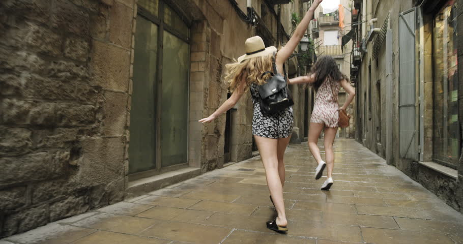 Best friends dancing in street in rain silly dance in rainy weather celebrating adventure Barcelona Spain