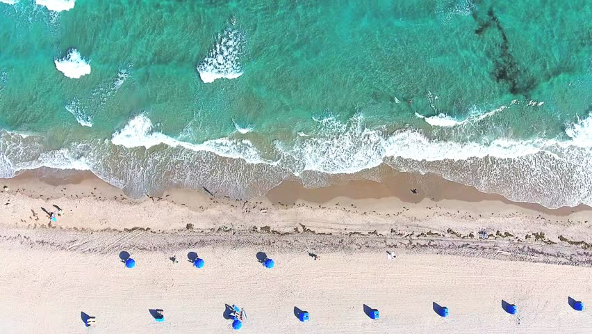 Video loop with aerial footage showing bird eye view with people walking and getting tan on a tropical Florida beach under blue umbrellas and turquoise ocean waves breaking against the coastal line | Shutterstock HD Video #24950414
