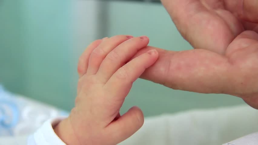 Mother and newborn daughter in maternity home. Hand in hand