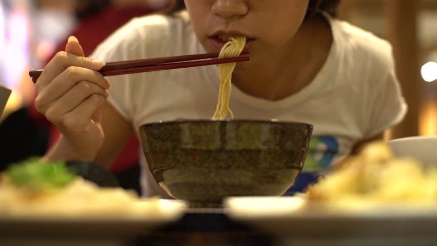 4K Asian woman eating beef noodles for dinner in a restaurant. Using sticks for eat the hot traditional chinese food-Dan #24974267