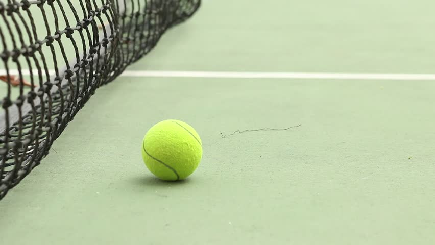 Rolling tennis ball on ground at green court with net #24974411