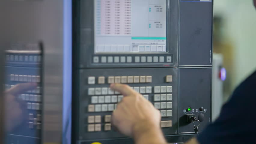 A man is standing in front of the screen and he is pushing the buttons very fast to navigate the whole production process. | Shutterstock HD Video #25006583