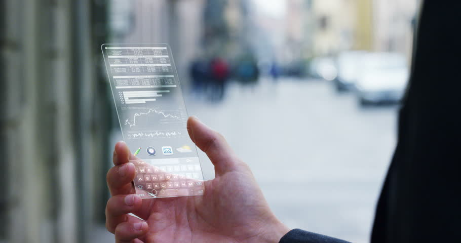 A businessman in the city,use the transparent phone with the latest technology to control finance and the markets of the financial bag. Concept:technology,business, immersive technology and future | Shutterstock HD Video #25019657