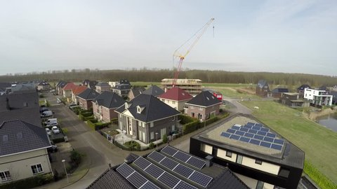 Aerial low flight bird view moving forwards over urban area new modern build houses with solar panels sun panels on roofs providing renewable energy by sunlight great new architecture 4k resolution