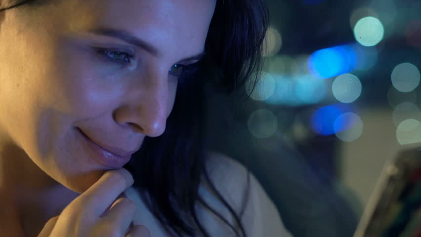 Happy, young woman watching movie on smartphone by window at night  #25030526