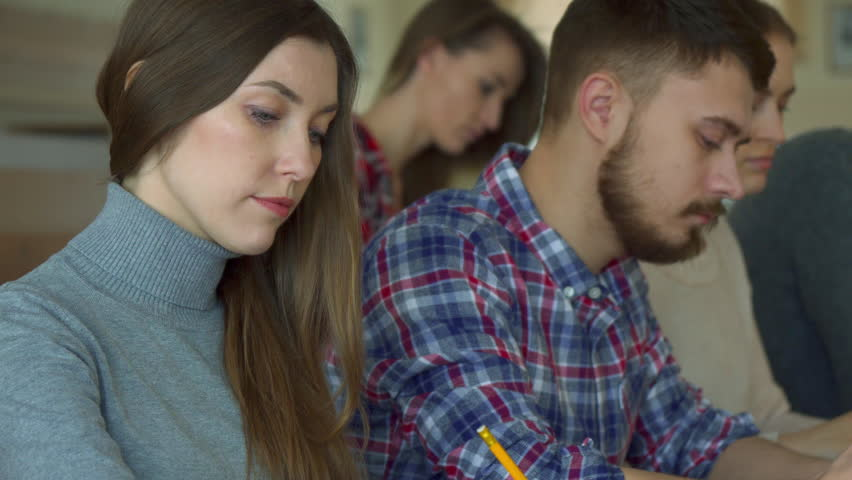 Young caucasian people studying at the college. Close up of pretty brunette girl smiling for the camera at the lecture hall. Attractive female student sitting against background of her bearded male #25033388