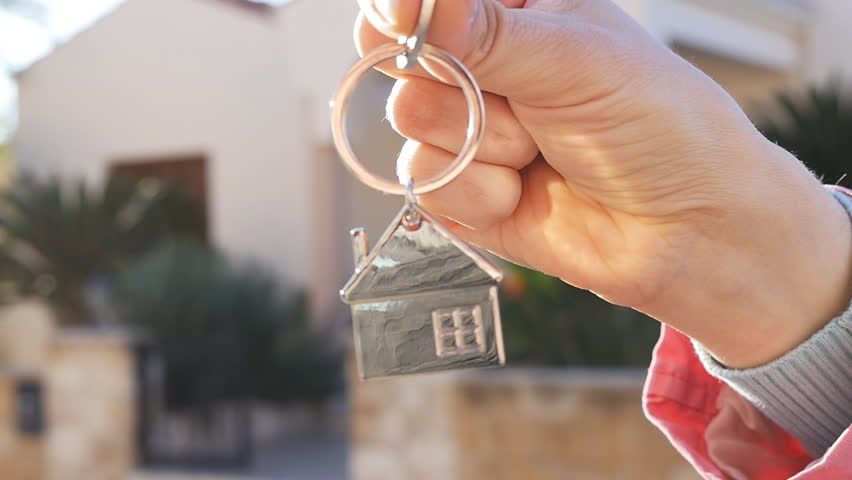 A hand is holding a key from the new home | Shutterstock HD Video #25035230