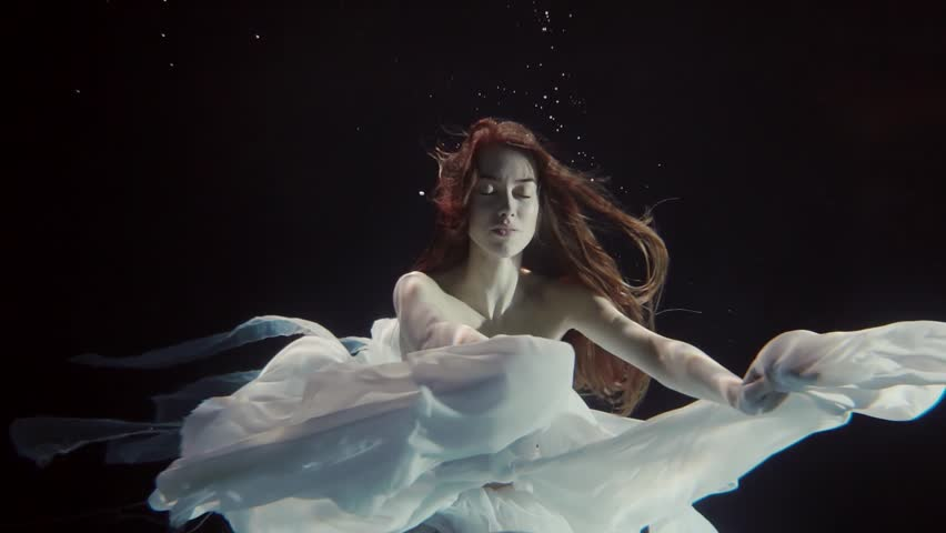 young woman with long red hair swimming underwater in a white dress like a fairy tale