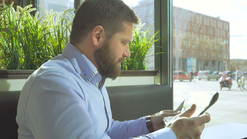 Businessman reading daily newspaper, profile in cafe, close steadycam shot | Shutterstock HD Video #25050902