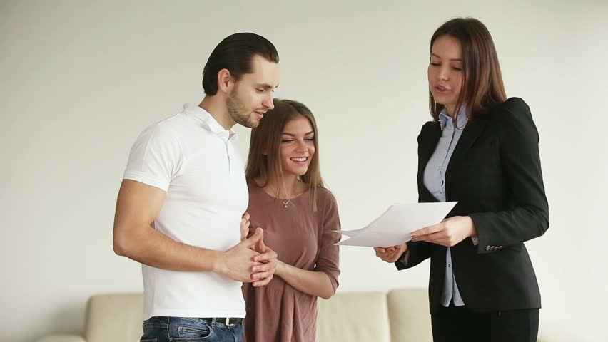 Young attractive happy smiling casual couple meeting consultant in office or at home. Cheerful husband and wife discussing contract and shaking hands with female contractor after reaching an agreement #25054565