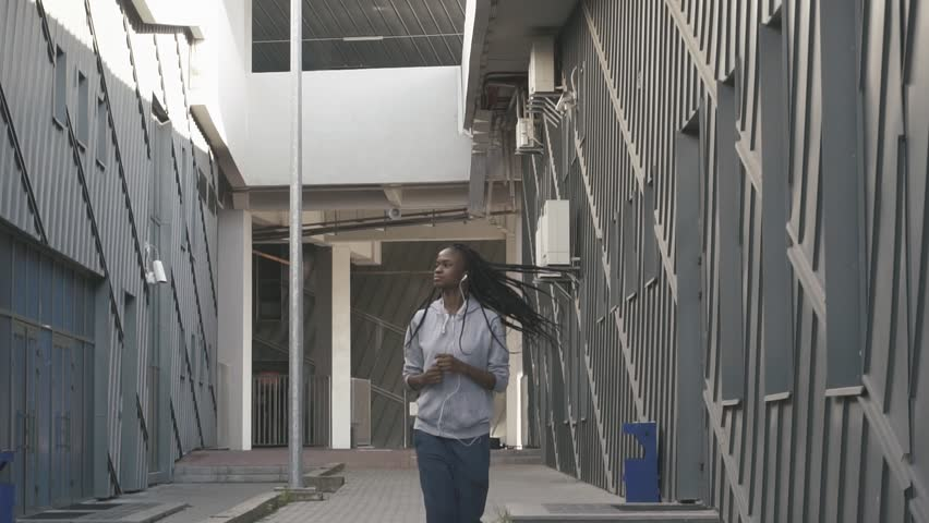 The jogging of the athlatic afro-american woman along the buildings. The model is listening to music #25058468