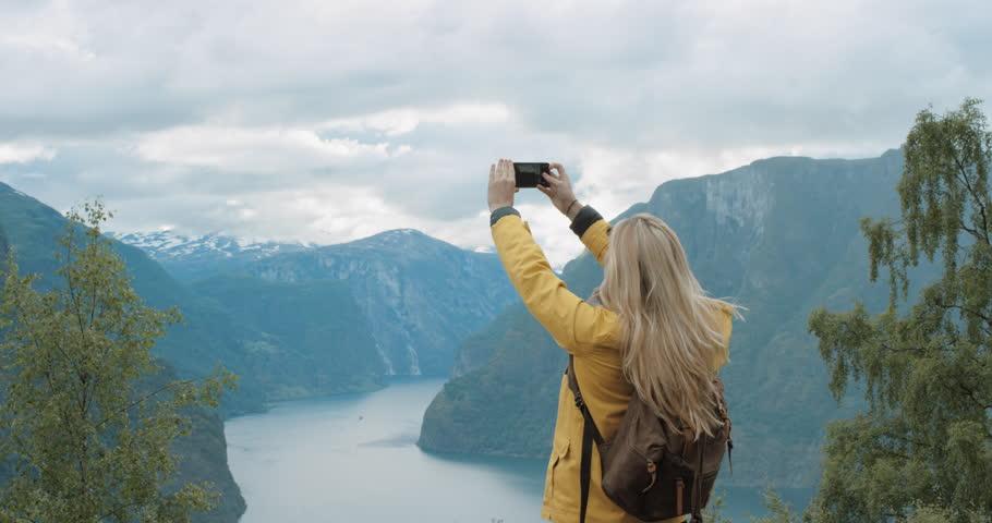 Woman taking photograph smartphone sharing photo of landscape nature background enjoying vacation holiday travel adventure