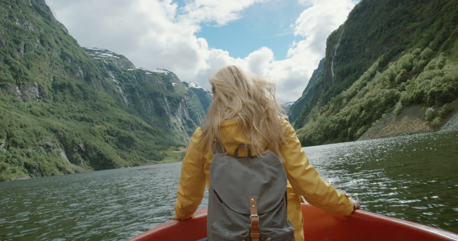 Woman lifting arms up sitting in boat on Fjord Norway hair blowing in wind celebrating scenic landscape nature background view enjoying vacation travel adventure