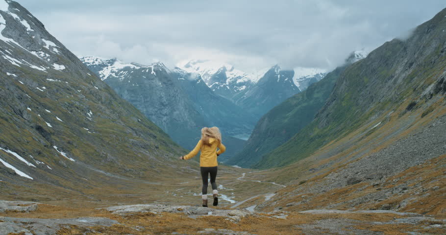 Woman dancing silly freestyle dance outdoors on mountain Crazy dancer girl having fun Independent traveller enjoying nature celebrating vacation travel adventure Norway | Shutterstock HD Video #25063097