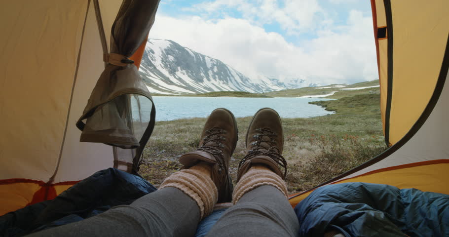 Camping woman lying in tent Close up of Girl feet wearing hiking boots relaxing on vacation POV #25063172