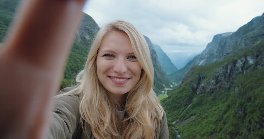 Beautiful woman having video chat using smartphone outdoors sharing travel adventure with friends Girl filming selfie video photo for social media with mobile phone enjoying Norway vacation | Shutterstock HD Video #25063334