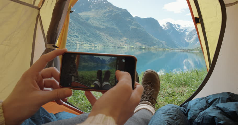 Camping woman lying in tent taking photo of feet with smart phone Close up of Girl wearing hiking boots relaxing on vacation POV Norway #25065458