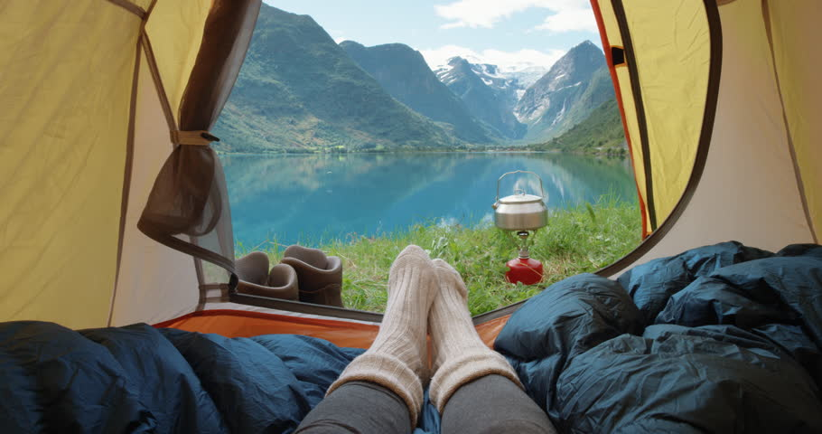 Camping woman lying in tent Close up of Girl feet wearing hiking boots relaxing on vacation POV #25065488
