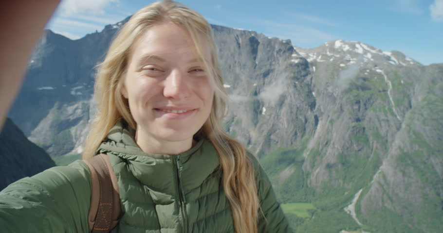 Beautiful woman taking selfie video using smartphone outdoors Girl sharing photograph on social media with mobile phone enjoying vacation travel adventure Romsdalen Valley Norway | Shutterstock HD Video #25065491