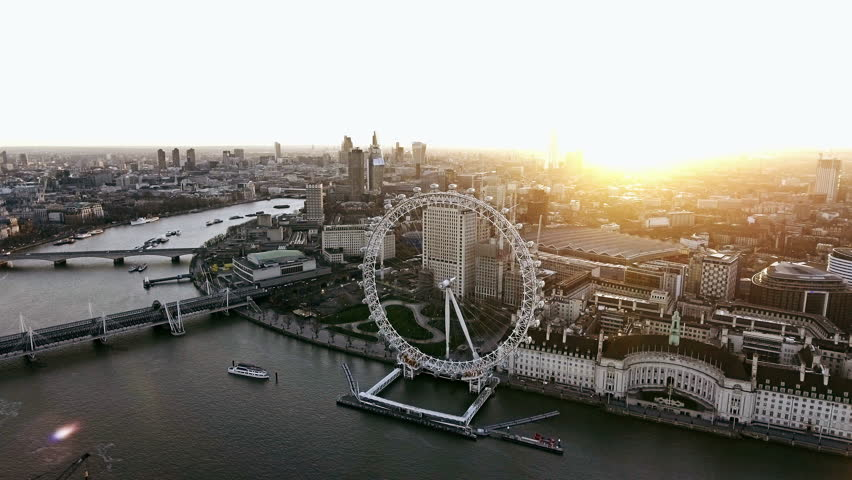 Panoramic Aerial Shot of Houses of Parliament & Big Ben in Central London features The London Eye Wheel, River Thames and Iconic Business Buildings Skyscrapers with Beautiful Sunrise 4K