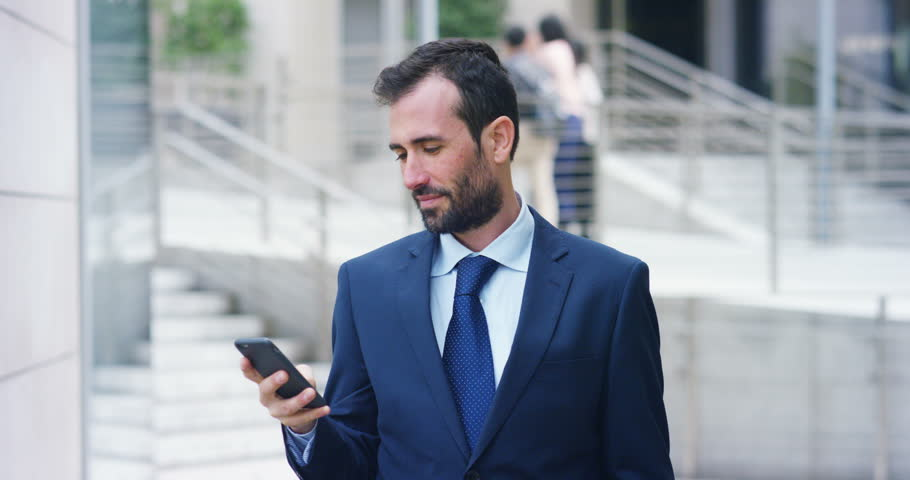 A businessman answering the phone, send messages and smiles for the beautiful job news and in the background you see a skyscraper. Concept: technology, telephony, business trips, business, wall street | Shutterstock HD Video #25082462
